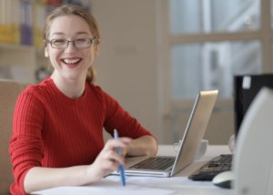 Woman smiles in front of computer