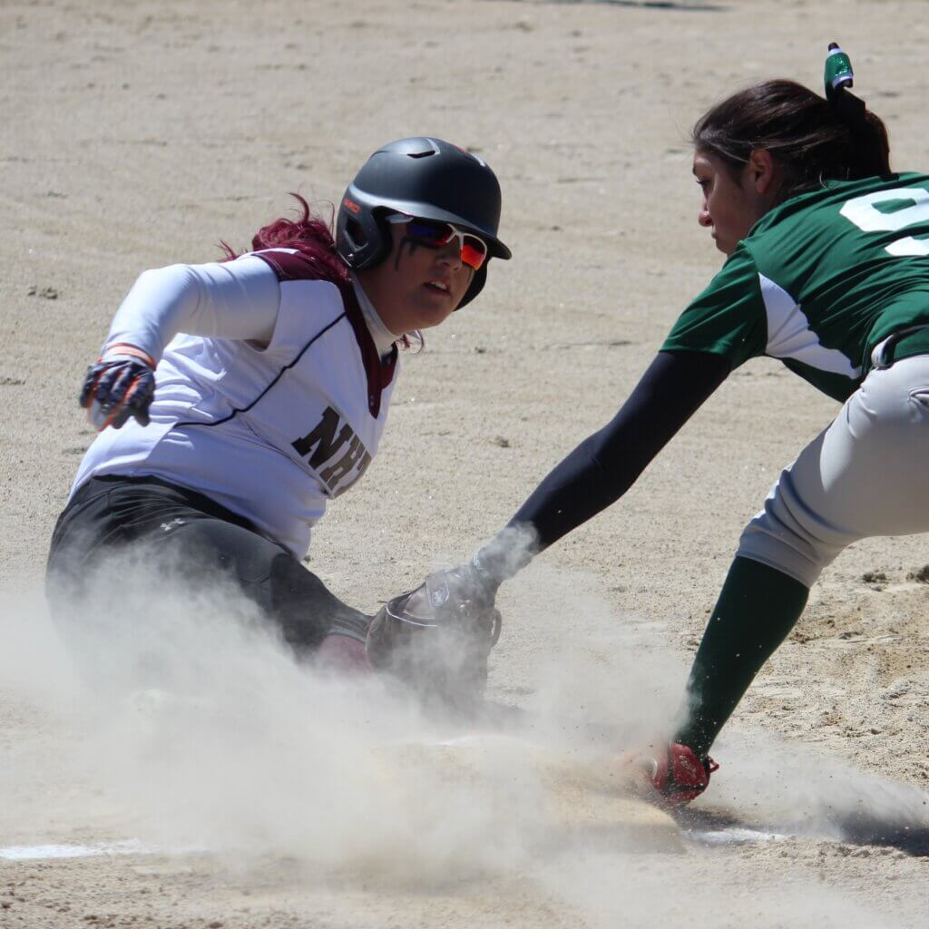 NHTI Women's Softball sliding into base